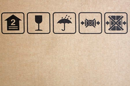 Black fragile symbol on cardboard, brown paper box.