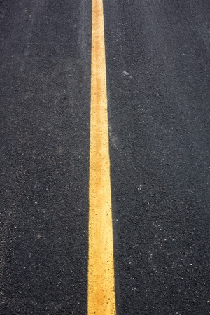 Black asphalt road, yellow lines separate lanes. photo