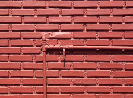 tuberias de agua: Pared de ladrillo rojo con las tuber�as de agua y la v�lvula de corte abierta.