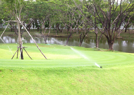 Sprinkler watering lawns, parks, golf courses, nature reasserted. photo