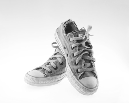 Old sneakers isolated on torn white background. photo