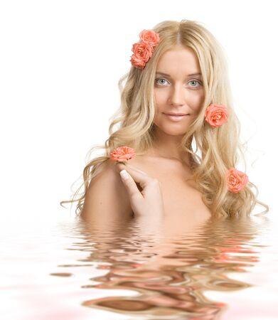 Le portrait d'une belle blonde dame rose avec des roses dans l'eau sur un fond blanc