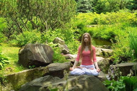 joga: Young girl practising yoga in the park on sunny day