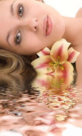Portrait de belle jeune femme dans l'eau sur fond blanc