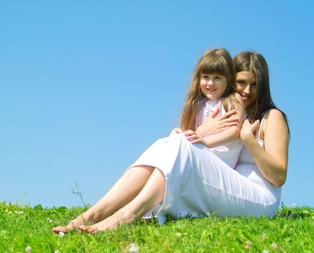 Mother and daughter resting in a park in sunny day photo