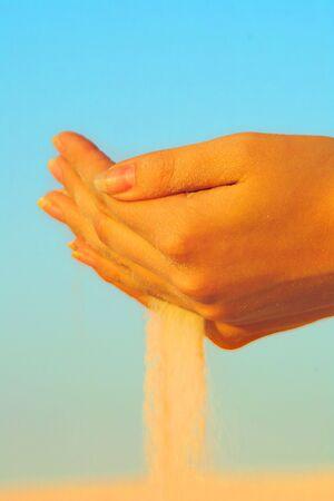 Mains exploitation de sable blanc sur le fond de ciel turquoise