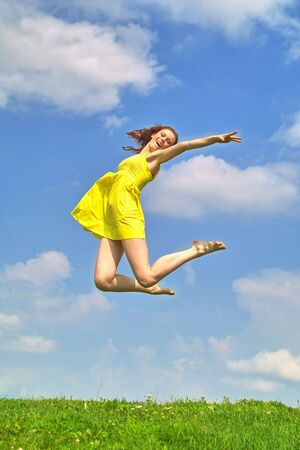 Young lady in yellow dress  jumping on the backgroud of the sky  photo