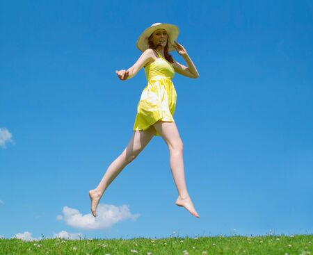Young lady in yellow dress and hat jumping on the backgroud of the sky  photo