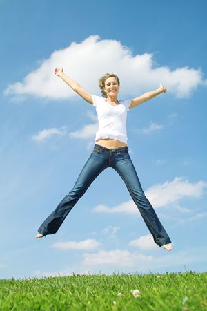 Beautiful lady in jeans jumping over blue sky