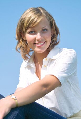 Beautiful lady in white smiling over sky Stock Photo