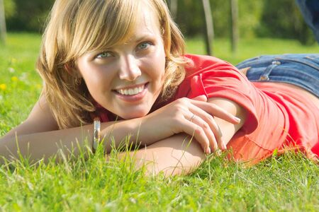 A beautiful lady lay on the grass in sunny day Stock Photo