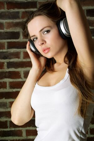 Portrait of beautiful young girl with headphones on the brick wall background photo