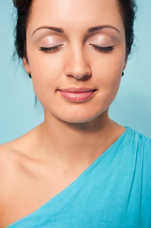 Portrait of young beautiful woman with closed eyes on a blue blackground photo