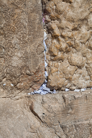 western wall: Lots of papers with the prayers of believers stuck in a crack in the Western wall in Jerusalem. Stock Photo