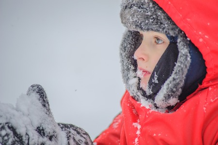 A blue eyed 8 years old boy licking his mitten and eating snow, close up portrait Reklamní fotografie