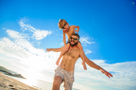 Eight years old boy sitting on dads shoulders. Both in swimming shorts and sunglasses, having fun on the beach. Bottom view. Blue sky and altocumulus clouds behind them