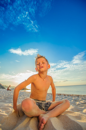 climas: Handsome eight years boy on beach playing with a stream of sand Foto de archivo