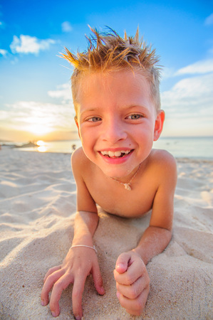 Handsome eight years boy on beach playing with a stream of sand Stock Photo