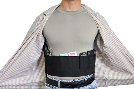 gat: Torso of a man dressed in civilian clothes, underneath the shirt there is a set for concealed carry weapons. Face hidden
