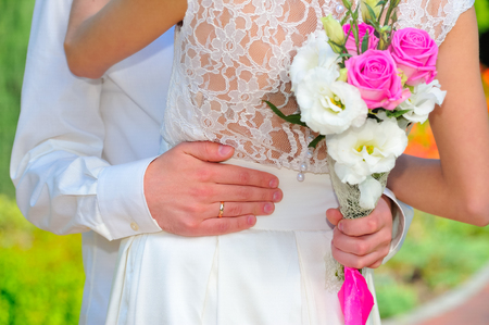 The wedding ring: groom hand embraces the waist of the bride. Wedding bouqet. Close up.