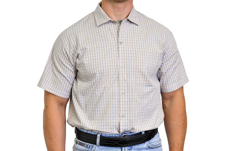 Torso of a man dressed in civilian clothes, underneath the shirt there is a set for concealed carry weapons. Face hidden