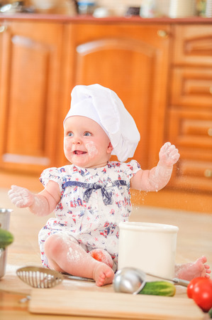 Cute liitle girl in chefs hat sitting on the kitchen floor soiled with flour, playing with food, making mess and having fun. Stock Photo