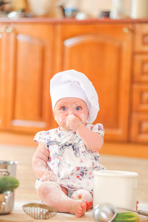 whiff: Cute liitle girl in chefs hat sitting on the kitchen floor soiled with flour, playing with food, making mess and having fun