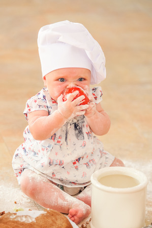 Cute liitle girl in chefs hat sitting on the kitchen floor soiled with flour, playing with food, making mess and having fun