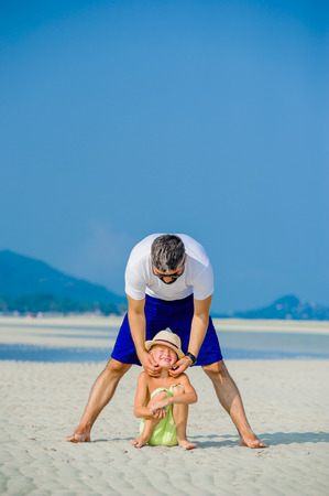thai ethnicity: Happy young family of three having fun on the desert sunny beach Stock Photo