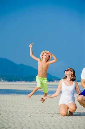 Mother and son having fun on the desert sunny beach Stock Photo