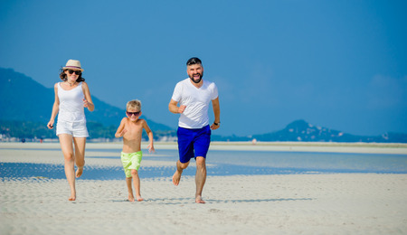 Happy young family of three having fun on the desert sunny beach Zdjęcie Seryjne
