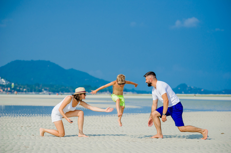 Happy young family of three having fun on the desert sunny beach Stock Photo