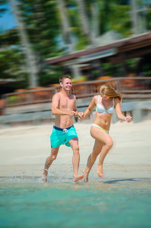 Young couple - newlyweds - having fun at the tropical beach of Ko Samui