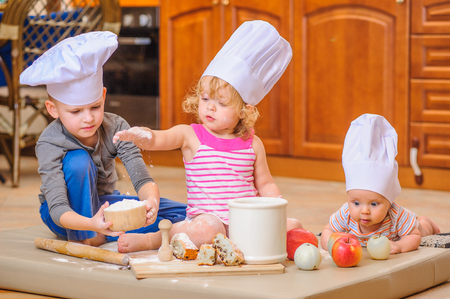 Two siblings - boy and girl - and a newborn kid with them in chefs hats sitting on the kitchen floor soiled with flour, playing with food, making mess and having fun