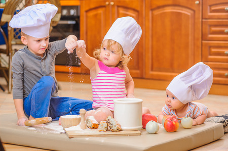 whiff: Two siblings - boy and girl - and a newborn kid with them in chefs hats sitting on the kitchen floor soiled with flour, playing with food, making mess and having fun