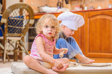 Two siblings - boy and girl - in chefs hats near the fireplace sitting on the kitchen floor soiled with flour, playing with food, making mess and having fun