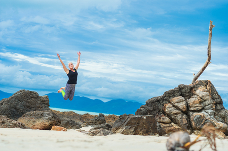 Beautiful mature aged woman jumps and having fun on a desert tropical beach. Stock Photo