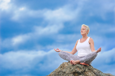 climas: Beautiful mature aged woman sits on top of a cliff doing yoga.