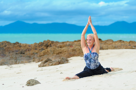 Beautiful mature aged woman doing yoga on a desert tropical beach.