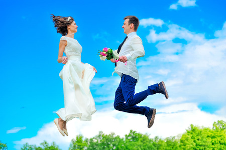 Young and handsome newlyweds are fluttering in the air Stock Photo