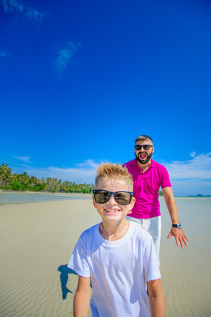The happiest childhood: father and son running along the tropical beach Stock Photo