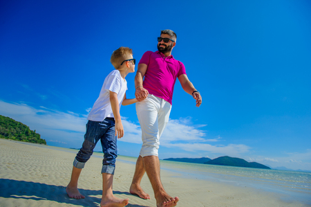 The happiest childhood: father and son walking along the tropical beach
