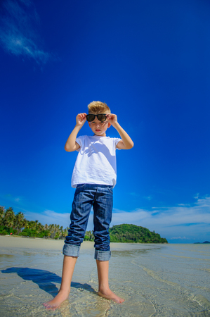 Aanbiddelijke jongen die pret op het tropische strand heeft. Wit t-shirt, donkere broek en zonnebril. Blootsvoets op wit zand Stockfoto