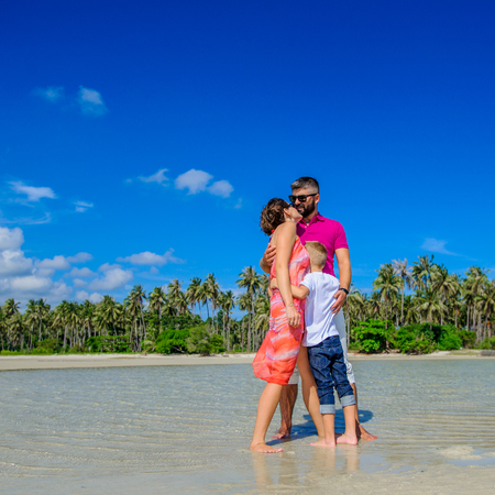 The happiest childhood: father, mother and son having fun on the tropical beach