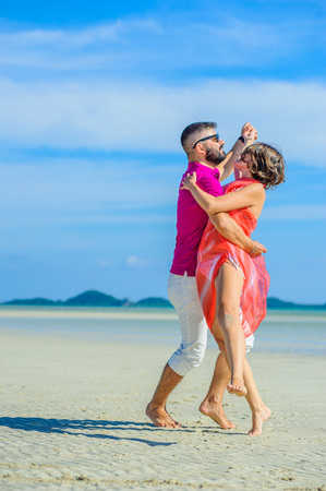 Happy married couple running and jumping along the tropical beach, laughing and enjoing time together. Dancing