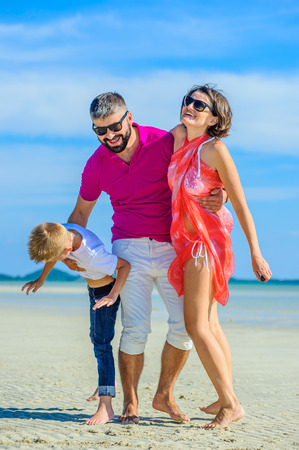 Happy family of three at the tropical beach, laughing and enjoing time together.