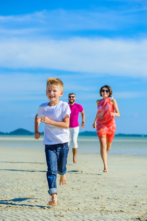 Family of three running and jumping along the tropical beach, laughing and enjoing time together