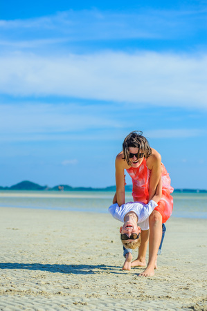 Dancing with mom. Happy family - mom and son - at the tropical beach, laughing and enjoing time together. Stock Photo