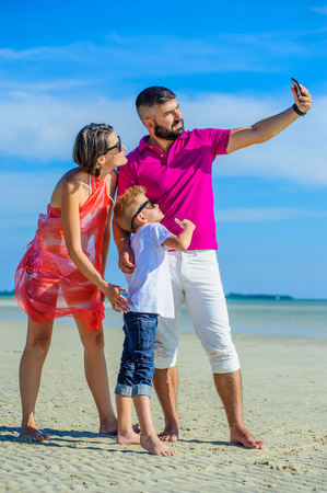 Happy family of three at the tropical beach, laughing and enjoing time together, taking selfies