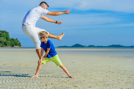 Happy father and son at the tropical beach, laughing and enjoing time together